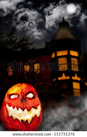 Evil Pumpkin - Jack O Lantern in front of Haunted House - stock photo