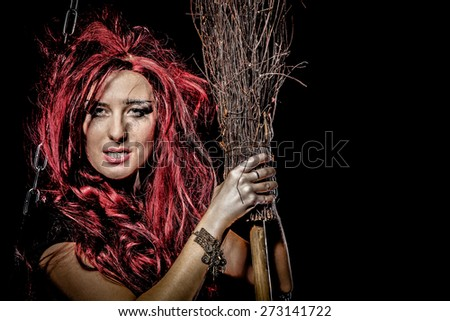 Evil red-haired witch and her broomstick - stock photo