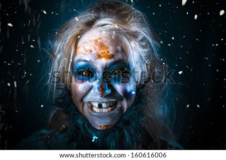 Evil winter monster smiling in chilling style beneath falling snow. Zombie elf