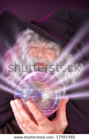 Evil wizard looking into his magic sphere - stock photo