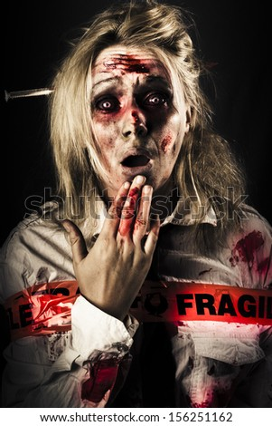 Evil zombie woman expressing fear and shock horror when awakening in a morgue wrapped in fragile postage tape, NDE or near death experience concept on black background