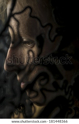 Evocative portrait of a woman in deep shadow throwing patterns across the side of her face with a serene thoughtful expression, close up of her profile.