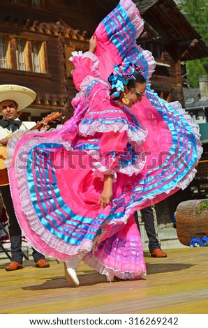 EVOLENE, SWITZERLAND - AUGUST 11: Mexican dancing girl from Guadelupe Omexochitl in the CIME mountain culture Festival: August 11, 2015 in Evolene, Switzerland - stock photo