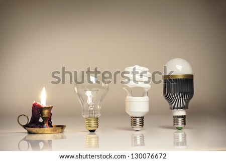 evolution of lighting, with candle, tungsten, fluorescent and LED bulb - stock photo