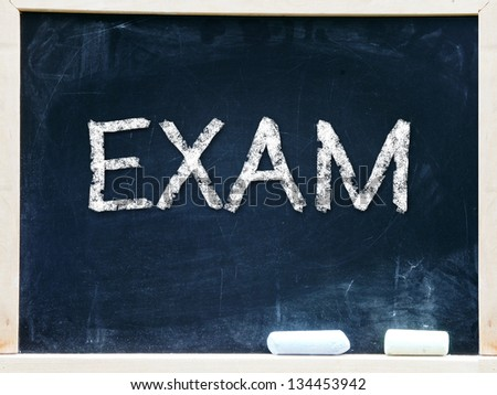 Exam handwritten with white chalk on a blackboard - stock photo