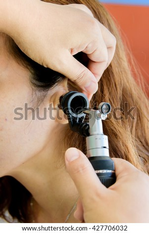 Examining ear of young woman with otoscope - stock photo
