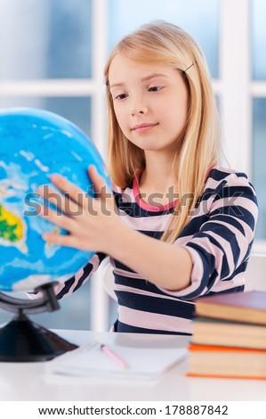 Examining globe. Cheerful little girl examining globe while sitting at the table - stock photo