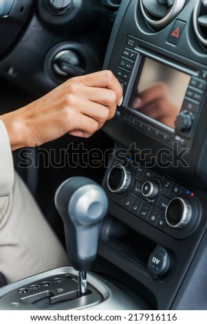 Examining her new car. Close-up of woman in formalwear touching dashboard with finger while sitting in car  - stock photo