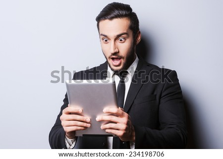 Examining his brand new tablet. Surprised young man in formalwear holding digital tablet while standing against grey background - stock photo