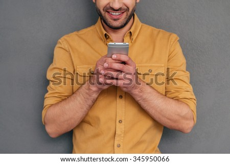 Examining his new smart phone. Cropped image of mature man holding smart phone and smiling while standing against grey background - stock photo
