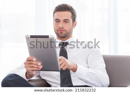Examining his new tablet. Confident young businessman in shirt and tie working on digital tablet while sitting at the chair - stock photo
