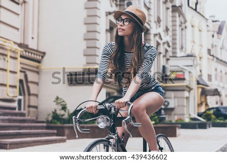Examining new places.  Beautiful young woman riding bicycle along the street and looking curious - stock photo