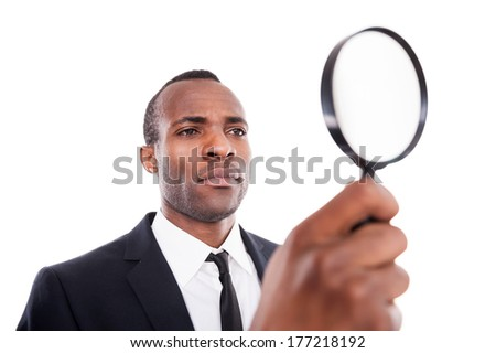 Examining something. Low angle view of serious young African man in formalwear looking through a magnifying glass while standing isolated on white background
