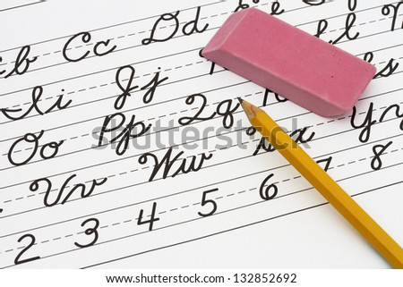 Example of cursive writing with a pencil and eraser, Learning cursive writing - stock photo