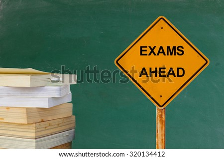 EXAMS AHEAD word on traffic sign with books and blackboard - stock photo