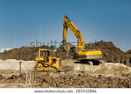 Excavator and bulldozer working at big construction site - stock photo