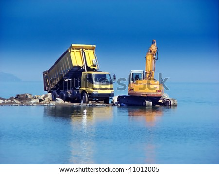 Excavator and dumper working in the sea - stock photo