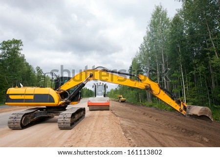 Excavator and roller compactor working during road construction - stock photo