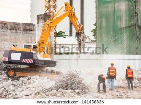 Excavator and Workers Working on Construction Site - stock photo