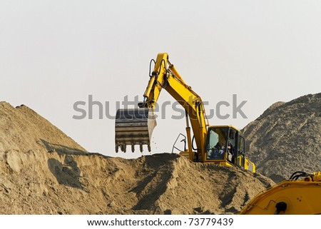 Excavator at big pile of sand at construction site