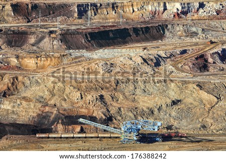 Excavator at the iron ore opencast mining  - stock photo