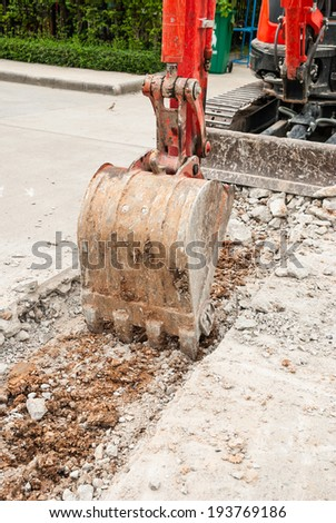 Excavator breaking concrete road surface. Shows part of the excavator bucket. - stock photo