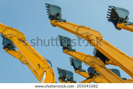 excavator bucket on the end of a yellow hydraulic arm of a digging machine. - stock photo
