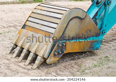 Excavator bucket on the sand - stock photo
