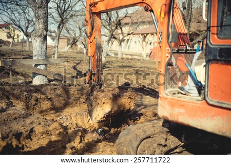 excavator, bulldozer and other machinery digging a foundation of house at construction site. Soft vintage effect - stock photo