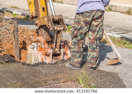 Excavator, bulldozer with workers work repair of pipe water and sewerage on road