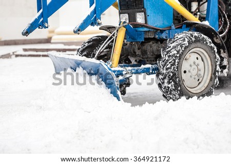 Excavator cleans the streets of large amounts of snow in city. Winter time concept. - stock photo
