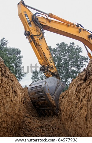 Excavator digging a deep trench - stock photo