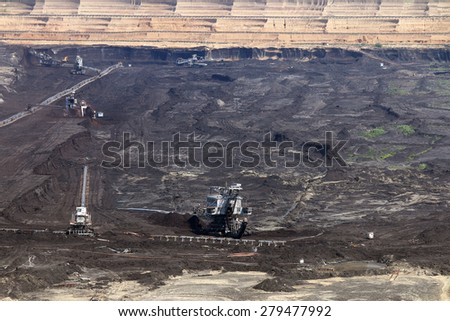 excavator digging and mining on open coal mine - stock photo