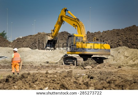 Excavator digging and moving earth at construction site - stock photo
