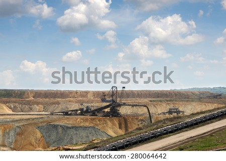 excavator digging on open pit coal mine - stock photo
