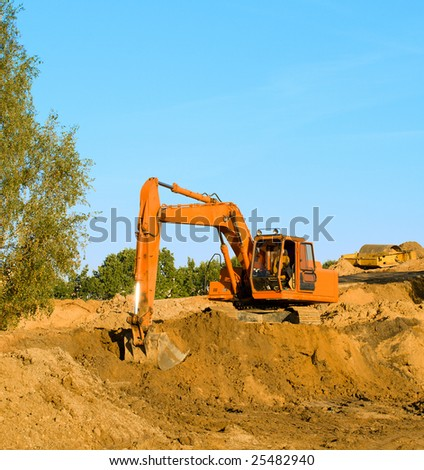 excavator digging sand on blue sky - stock photo