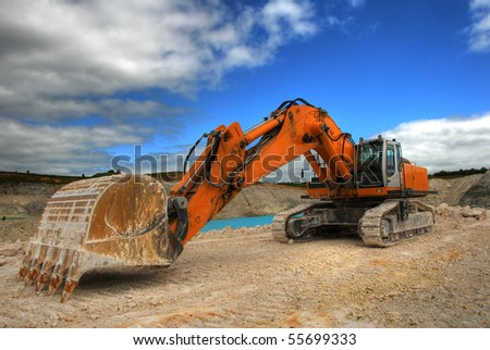 Excavator in a limestone quarry - stock photo