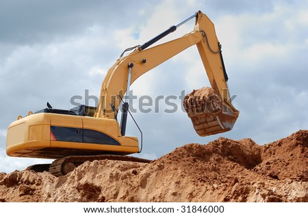 Excavator in sandpit with raised bucket (rear view)