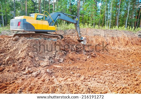 excavator in work on constructon site in forest - stock photo