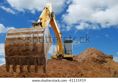 Excavator Loader standing in sandpit with pulled down bucket over cloudscape sky - stock photo
