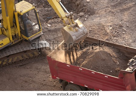 Excavator loading a truck on a construction site - stock photo