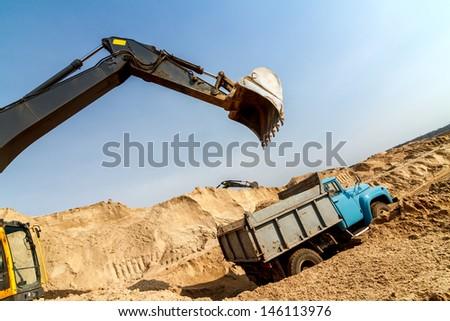 Excavator Loading Dumper Truck at Construction Site - stock photo