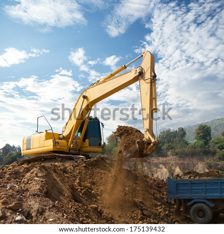 Excavator loading dumper truck tipper in construction site - stock photo