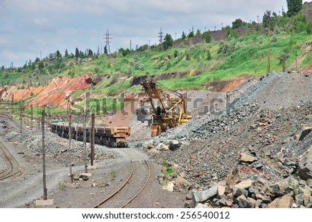Excavator loading iron ore to the train on the opencast mining site - stock photo