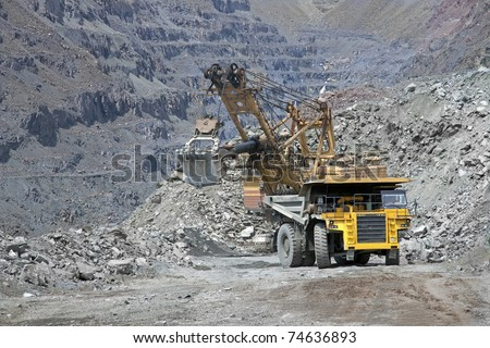 Excavator loading the iron ore into the heavy mining truck - stock photo