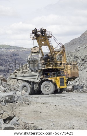Excavator loading the ore to the truck on the the opencast mining site - stock photo