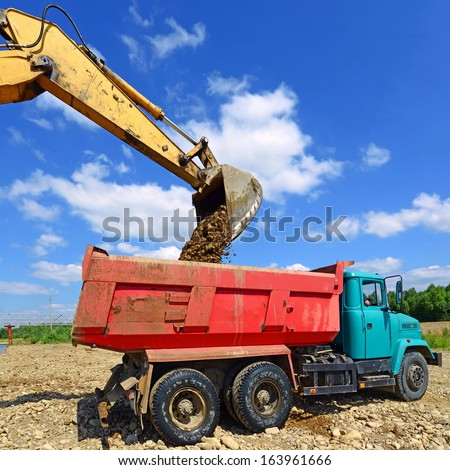 Excavator loads gravel car. - stock photo
