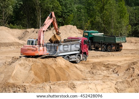 Excavator loads the ground in the truck at a construction site - stock photo