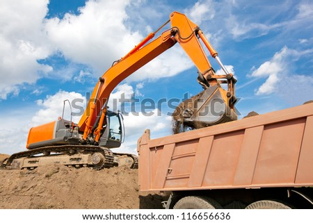 Excavator machine loading soil or sand into truck body - stock photo