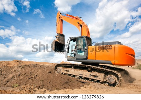 Excavator machine moves with raised bucket on construction site during earth moving works